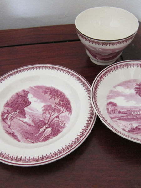 Victorian-era Wedgwood Etruria of dark fuschia landscape and people images. Set includes handle-less cup which was used to pour tea into the deep saucer and from which users sipped their tea. The plate was used either for biscuits or for a place to set down the deep-bowled saucer.
